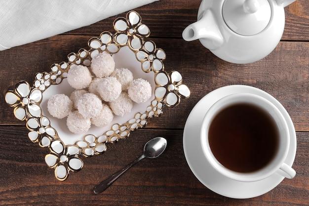 茶色の木製のテーブルの上にお茶と花瓶のおいしい甘いココナッツキャンディー。上からの眺め