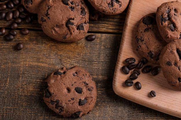 茶色の木製テーブルにチョコレートとコーヒーの粒が入ったおいしい甘いクッキー。上からの眺め