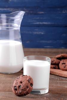 茶色の木製テーブルと青い背景にチョコレートとミルクのおいしい甘いクッキー