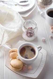 美しい甘いマカロンと白い木の背景にコーヒーカップ
