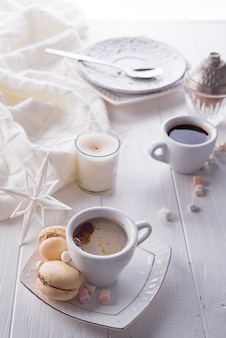 Tasty sweet macarons and coffee cup on white wooden background