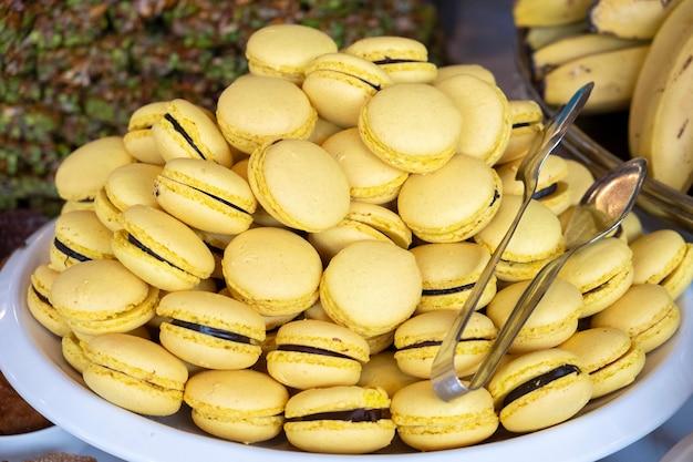 おいしい甘いマカロン。皿の上の黄色いマカロン。閉じる