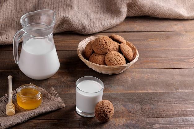 茶色の木製テーブルにミルクと蜂蜜が入ったおいしい甘いオートミールクッキー。