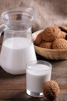 茶色の木製テーブルにミルクとおいしい甘いオートミールクッキー。