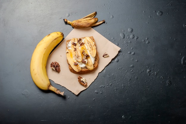 Tasty sweet sandwiches with bananas, nuts and chocolate,  on black table