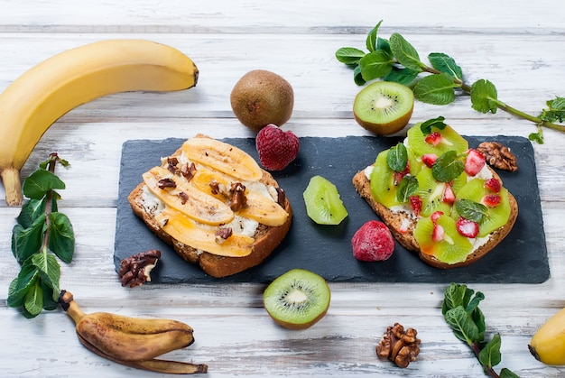 Tasty sweet sandwiches with bananas, nuts and chocolate, kiwi, strawberries and mint on wooden table