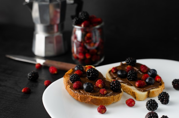 Tasty sweet toast with fresh berries and coffee for breakfast on dark background.