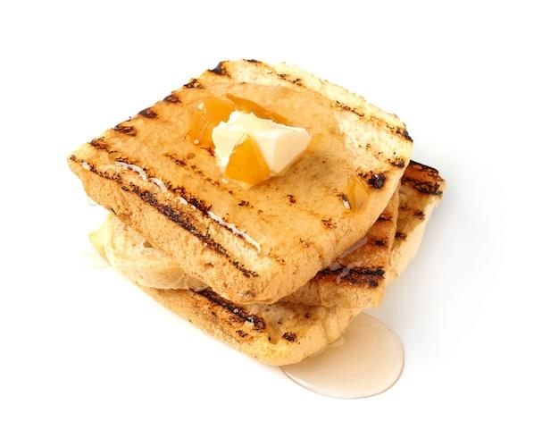 白い背景にバター、フルーツ、蜂蜜とおいしい甘いトースト