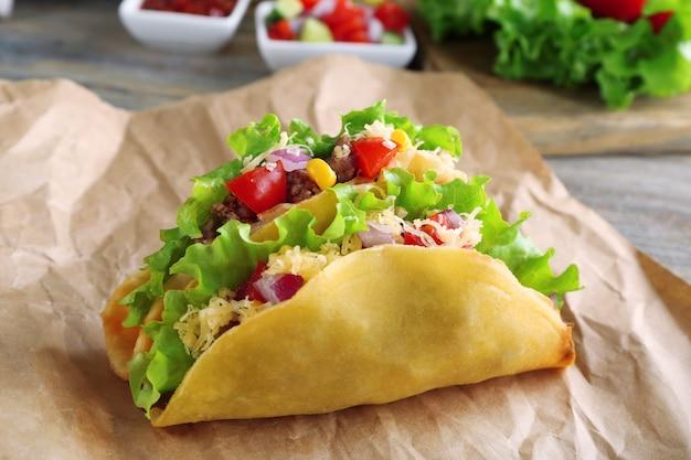 テーブルの上の紙に野菜とおいしいタコスをクローズアップ