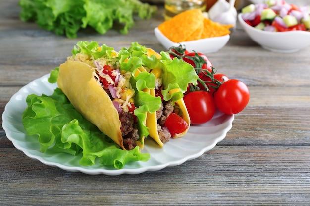 テーブルの上の皿に野菜を添えたおいしいタコスをクローズ アップ Premium写真