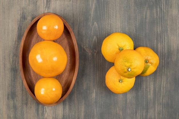 Gustosi mandarini o mandarini su una tavola di legno. foto di alta qualità