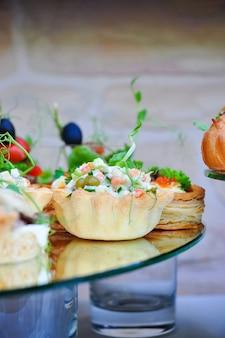 Вкусная тарталетка с салатом оливье на ресепшене крупным планом