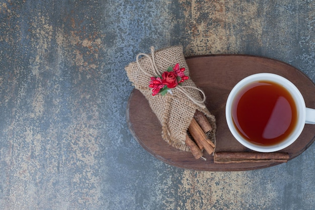 Tasty tea in white cup with cinnamon sticks on wooden board.