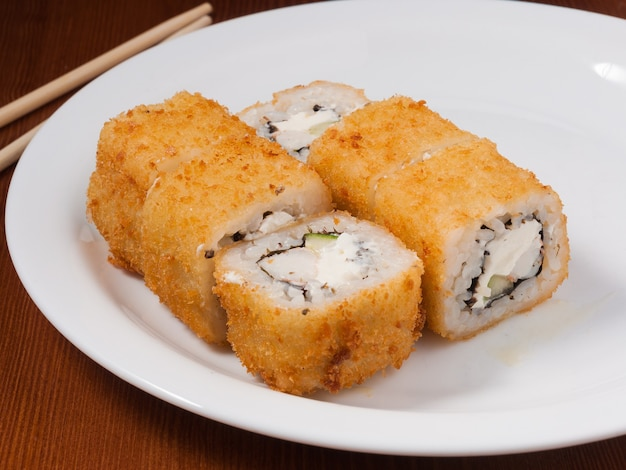 白い皿に海老を乗せた美味しい天ぷら巻き寿司