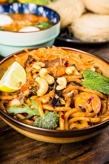 Tasty thai udon noodles with beef; broccoli; mint; nuts and lemon in bowl on wooden table