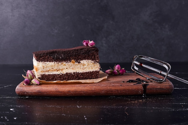 Gustosa torta tiramisù con semi di fiori su sfondo scuro.