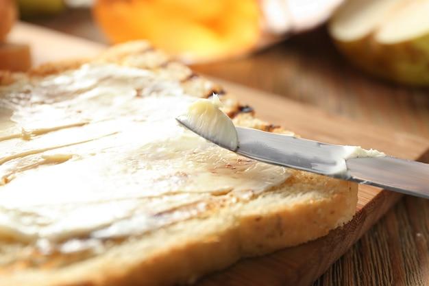 木の板にバターを添えたおいしいトースト、クローズアップ