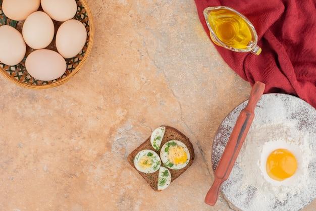 Gustoso toast con diverse uova e olio su tavola di marmo.