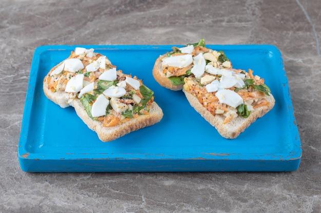 Tasty toast with sliced vegetables on blue plate.