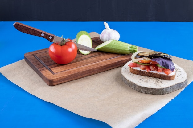 Tasty toast with vegetables on wood piece with tomatoes and zucchini.