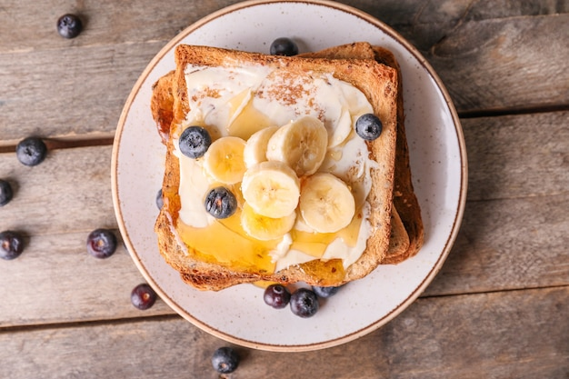 Tasty toasted bread with honey, butter and fruits on plate