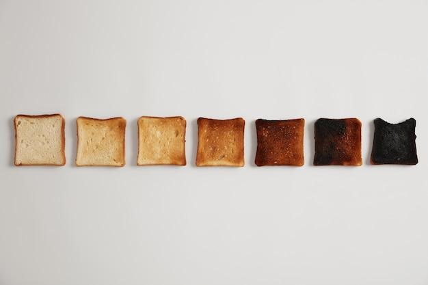 焼きたてから焦げたものまで、おいしいトーストしたパンのスライス。トーストの段階。セレクティブフォーカス。無愛想な美味しいおやつ。白い表面。それぞれがより長い時間、焙煎の程度でトーストされたトーストのセット。