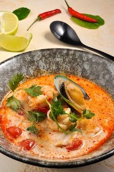 해산물을 곁들인 맛있는 톰 얌 수프를 닫습니다.