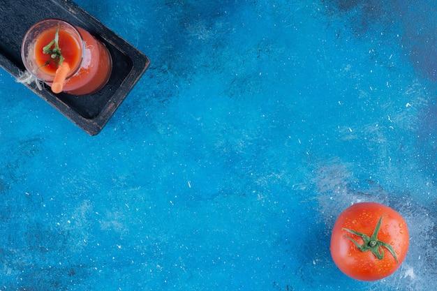 おいしいトマトジュースと青い背景のトマト。高品質の写真