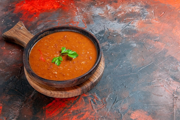 Tasty tomato soup on a brown cutting board on the right side of a mixed color table