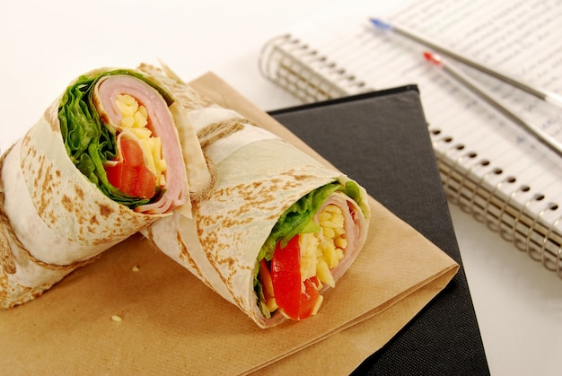Tasty tortilla wrap on a paper bag