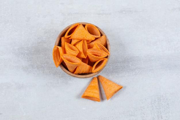Вкусные чипсы треугольника в деревянной миске.