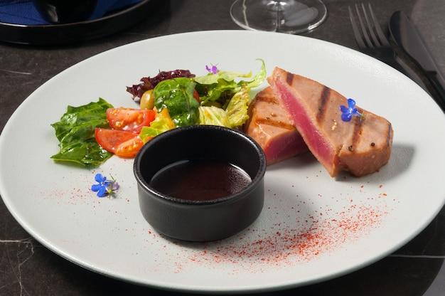 Вкусный стейк из тунца со свежими овощами и соусом