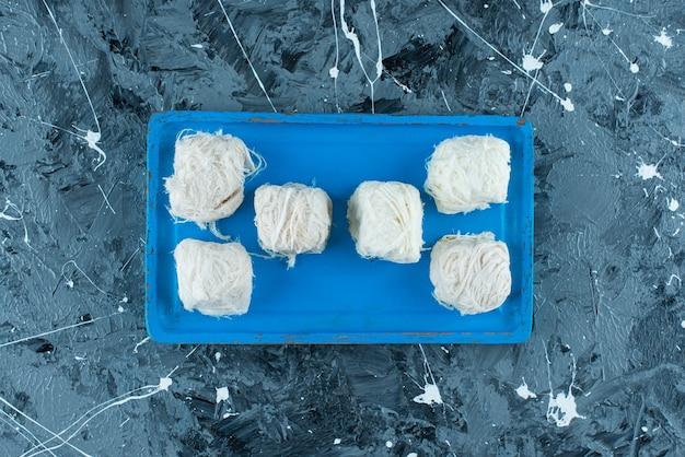 Вкусные турецкие хлопковые конфеты на деревянной тарелке, на синем фоне.