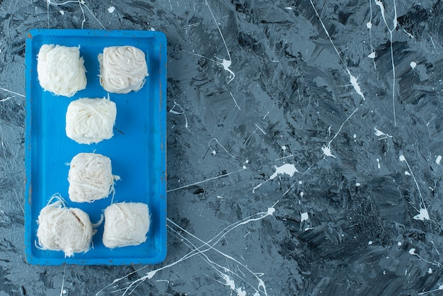 Gustose caramelle di cotone turche su un piatto di legno, sul tavolo blu.