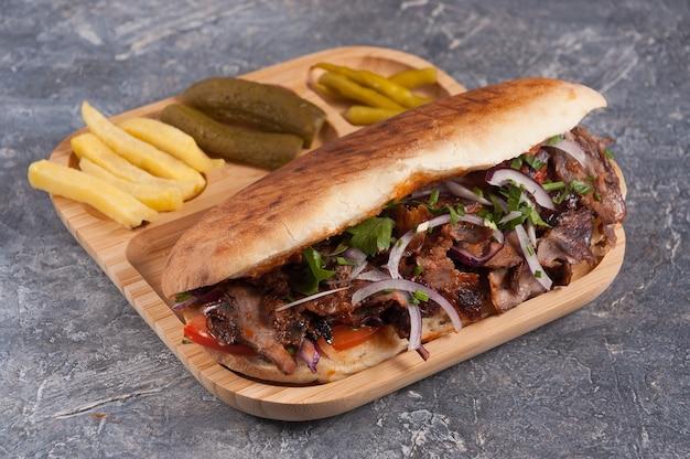 Вкусный турецкий донер с телятиной в косточке с картофелем фри и солеными огурцами и красным луком