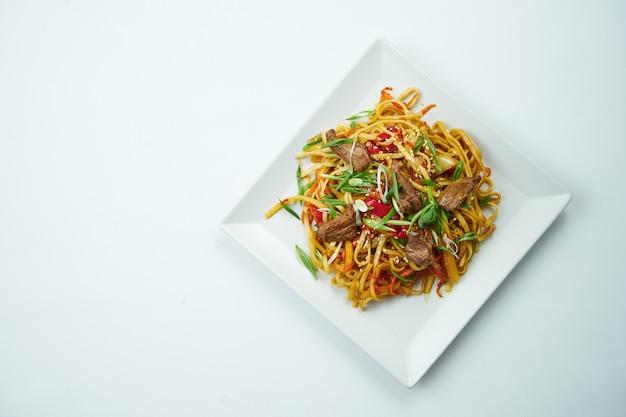 야채와 쇠고기 회색 테이블에 하얀 접시에 새 콤 하 고 달콤한 소스에 맛있는 우동. 복사 공간이있는 평면도