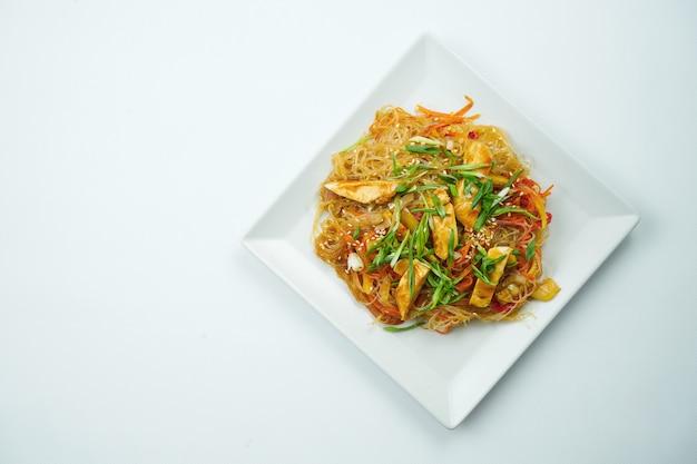회색 테이블에 야채와 닭고기 접시와 달 콤 하 고 신 소스에 맛있는 우동. 복사 공간이있는 평면도