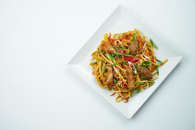 회색 테이블에 야채와 돼지 고기 접시와 달 콤 하 고 신 소스에 맛있는 우동. 복사 공간이있는 평면도