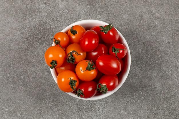 Gustosi pomodori acerbi nella ciotola, sul marmo.