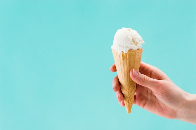 Tasty vanilla ice cream in hand on blue background