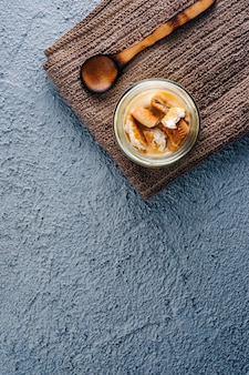 Tasty vanilla pudding on blue wooden background.