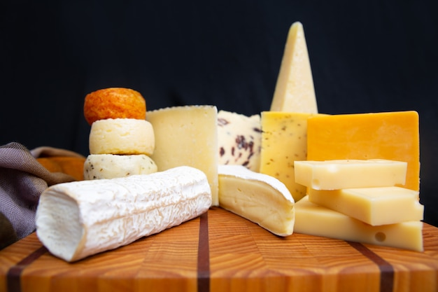 Tasty various cheeses laying on wooden board