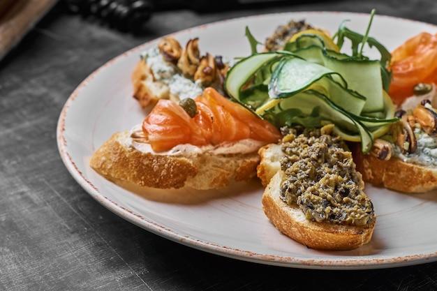 Вкусные различные итальянские бутерброды с морепродуктами на деревенском деревянном фоне. кростини с сыром, красной рыбой, лимоном и нарезанными оливками, горизонтальный вид с селективным фокусом