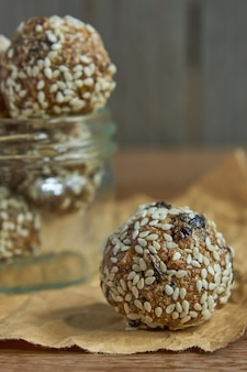Tasty vegan raw protein truffles or energy balls with prunes, seeds and nuts in a jar on wooden