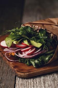 木製のテーブルの上のおいしいビーガンサンドイッチ