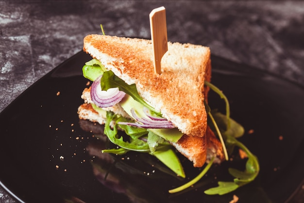 Tasty vegan sandwich with avocado and salad on a dark plate