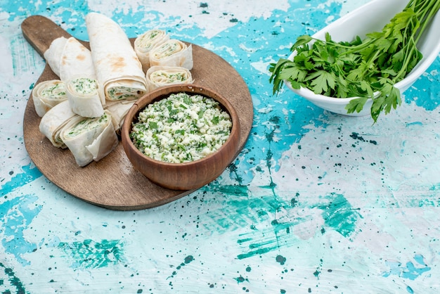 Gustosi involtini di verdure intere e affettate con ripieno di verdure e insalata di cavolo sulla scrivania luminosa, pranzo con spuntino a base di verdure