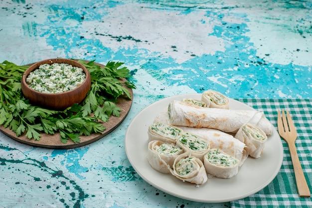 Gustosi involtini di verdure intere e affettate con verdure e insalata sulla scrivania blu