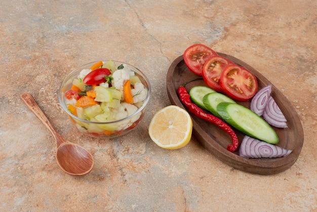 大理石の上にトマト、キュウリ、タマネギの木の板とガラスプレート上のおいしい野菜