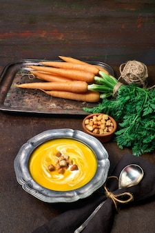 Tasty vegetarian carrot soup served with cream croutons in metal pewter bow